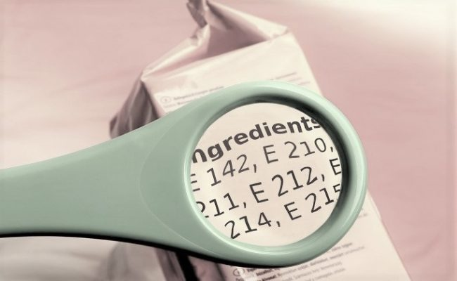 reading ingredients list on food package with magnifying glass. Magnifying glass on food additives label.